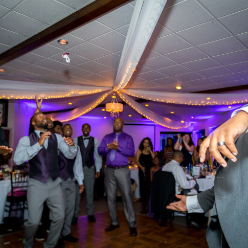 Groomsmen Throwing Garter to Groomsmen at a wedding for Finally Forever Photography