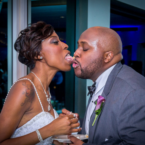 Bride licking her Grooms face after cutting the cake
