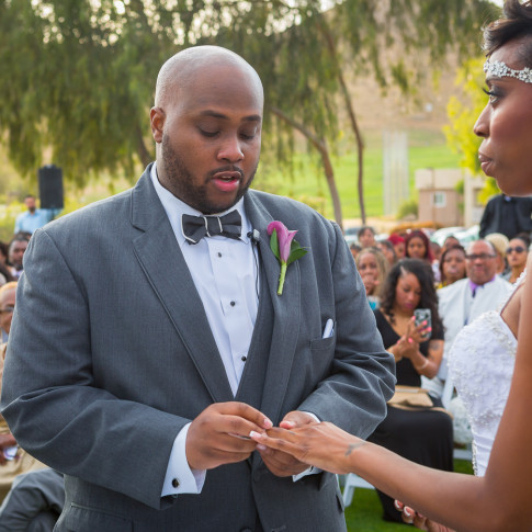 Groom putting ring on emotional bride at outdoor wedding ceremony at Hidden Valley Golf Course, Corona, CA.