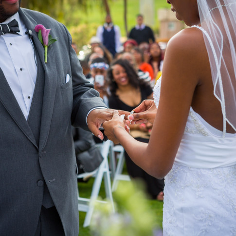 Bride putting a ring on the groom at an outdoor wedding ceremony Hidden Valley Golf Course in Corona, CA.