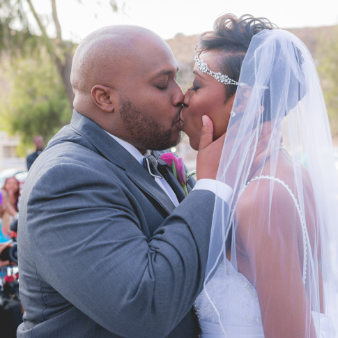 Black couple first kiss outdoor wedding ceremony Hidden Valley Golf Course, Corona, CA.