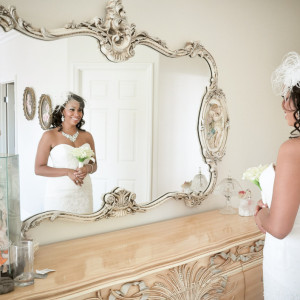 Beautiful bride looking in the mirror before wedding ceremony