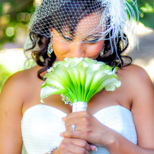 Beautiful black bride smelling lily bouquet