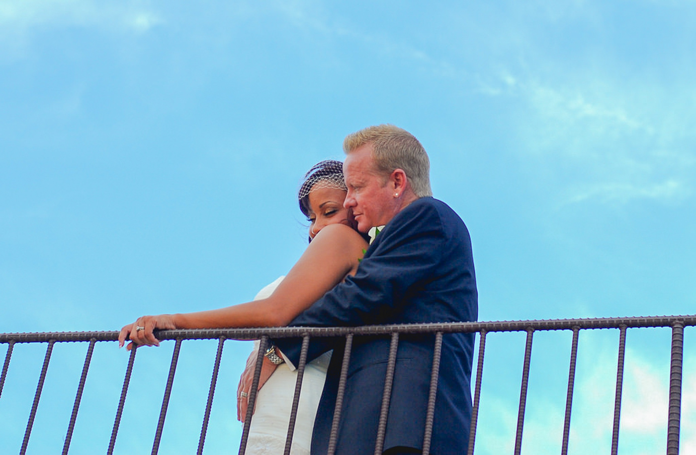 Bride and groom looking over railing at orang county mining co