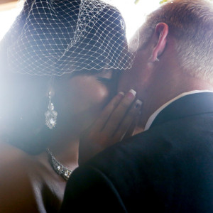 Bride and groom sharing first kiss at wedding ceremony at orange county mining co
