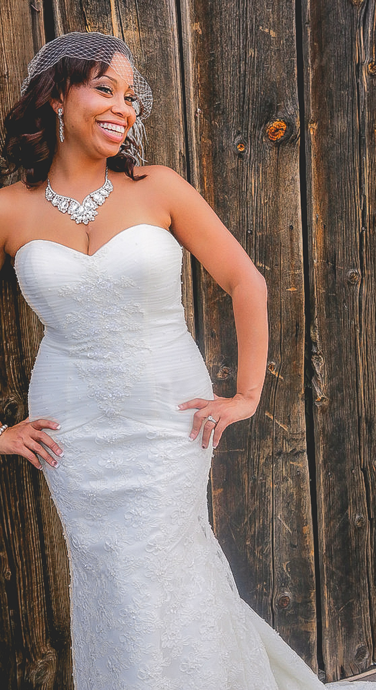 Smiling bride takes picture against old wood at orange county mining co