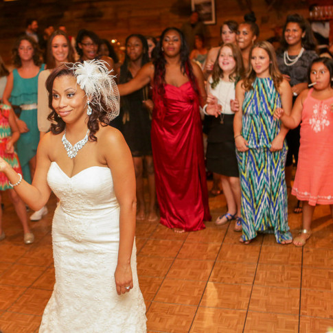Bride throwing bouquet at wedding reception at orange county mining co