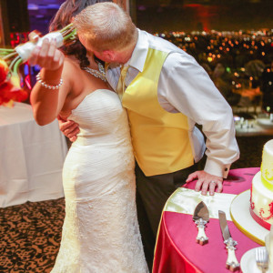 Bride and groom kissing before cutting cake at orange county mining co