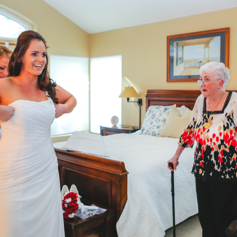Mother helping beautiful bride get ready for backyard wedding