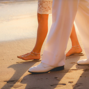 Couple in white walking down the beach at wedding ceremony. San Clemente