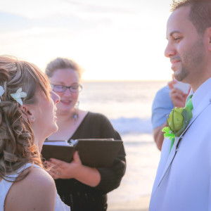 Smiling bride looking at groom during sunset beach wedding ceremony