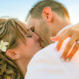 Bride and groom sharing first kiss at their beautiful sunset beach wedding.