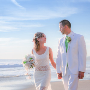 Bride and groom holding hand and walking on the beach during beach wedding ceremony