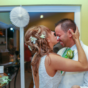 Bride licking cake off groom's face during wedding reception.