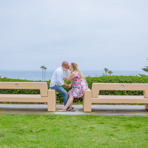 Couple kissing on benches in Newport beach engagement photo session