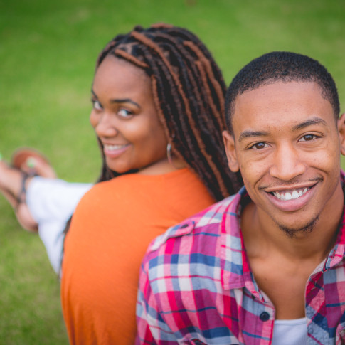 Black couple engagement photo on the grass at park