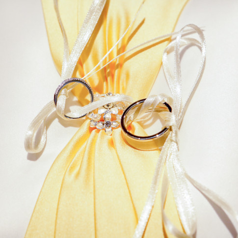 Wedding rings tied to ring pillow. Finally Forever Photography