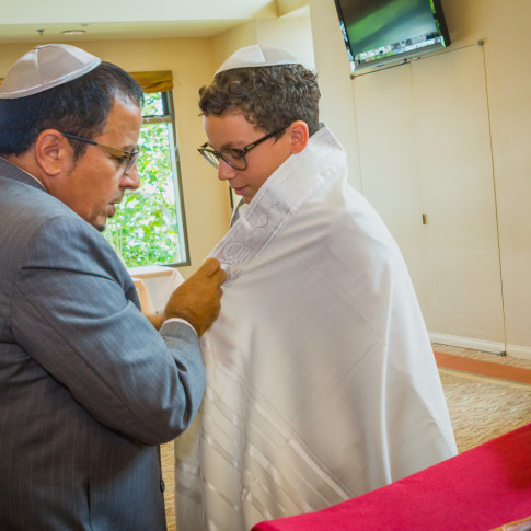 Father dressing son for bar mitzvah ceremony in Irvine