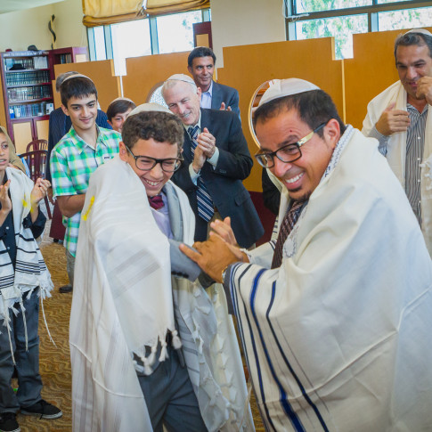 Father and son celebrating in a crowd at bar mitzvah ceremony