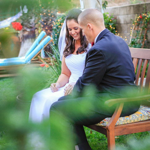 Bride and groom sitting on bench at backyard wedding ceremony