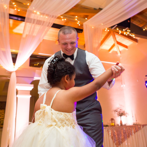 Groom dances with cute flower girl at a wedding