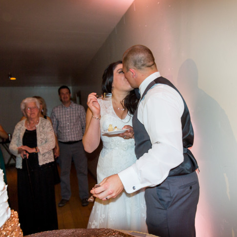 Bride and groom kiss after cutting cake at wedding reception at The Pierpont Inn, Ventura, CA.