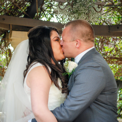 First kiss at a beautiful outdoor wedding ceremony in Ventura, CA. Finally Forever Photography