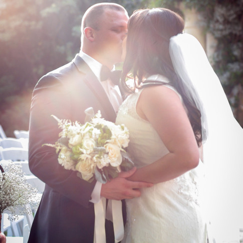 Bride and Groom kissing in the ceremony aisle at a beautiful outdoor wedding. Finally Forever Photography.