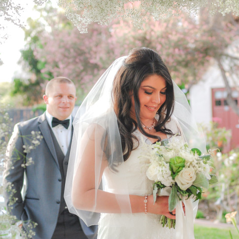 Blushing bride and groom under baby's breath wedding arch. Finally Forever Photography