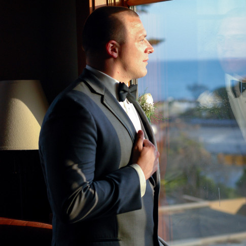 Groom looking out the window at the Pierpont Inn in Ventura, CA. Finally Forever Photography