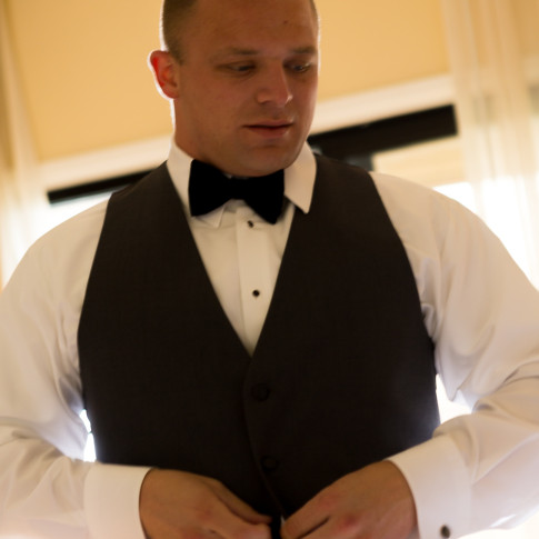 Groom putting on his tux getting ready for his big day