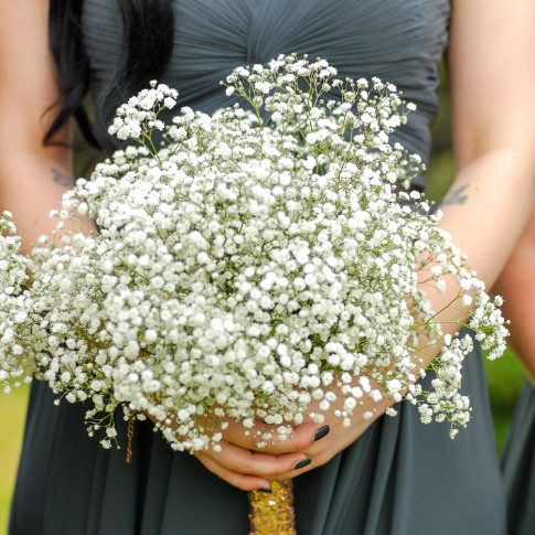 Bridesmaid holding bouquet at outdoor wedding ceremony at the Pierpont inn in Ventura, CA.