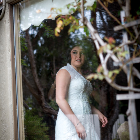 Bride looking out the window as she gets ready. Finally Forever Photography