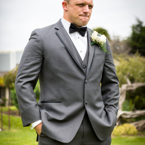 Groom in grey suit at an outdoor wedding ceremony. Finally Forever Photography