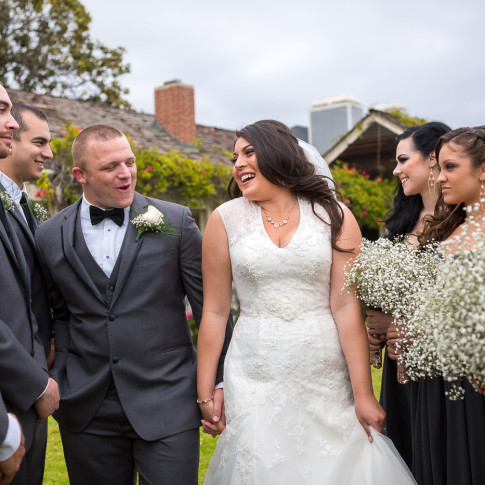 Smiling couple posing with bridesmaids and groomsmen at wedding ceremony. Finally Forever Photography