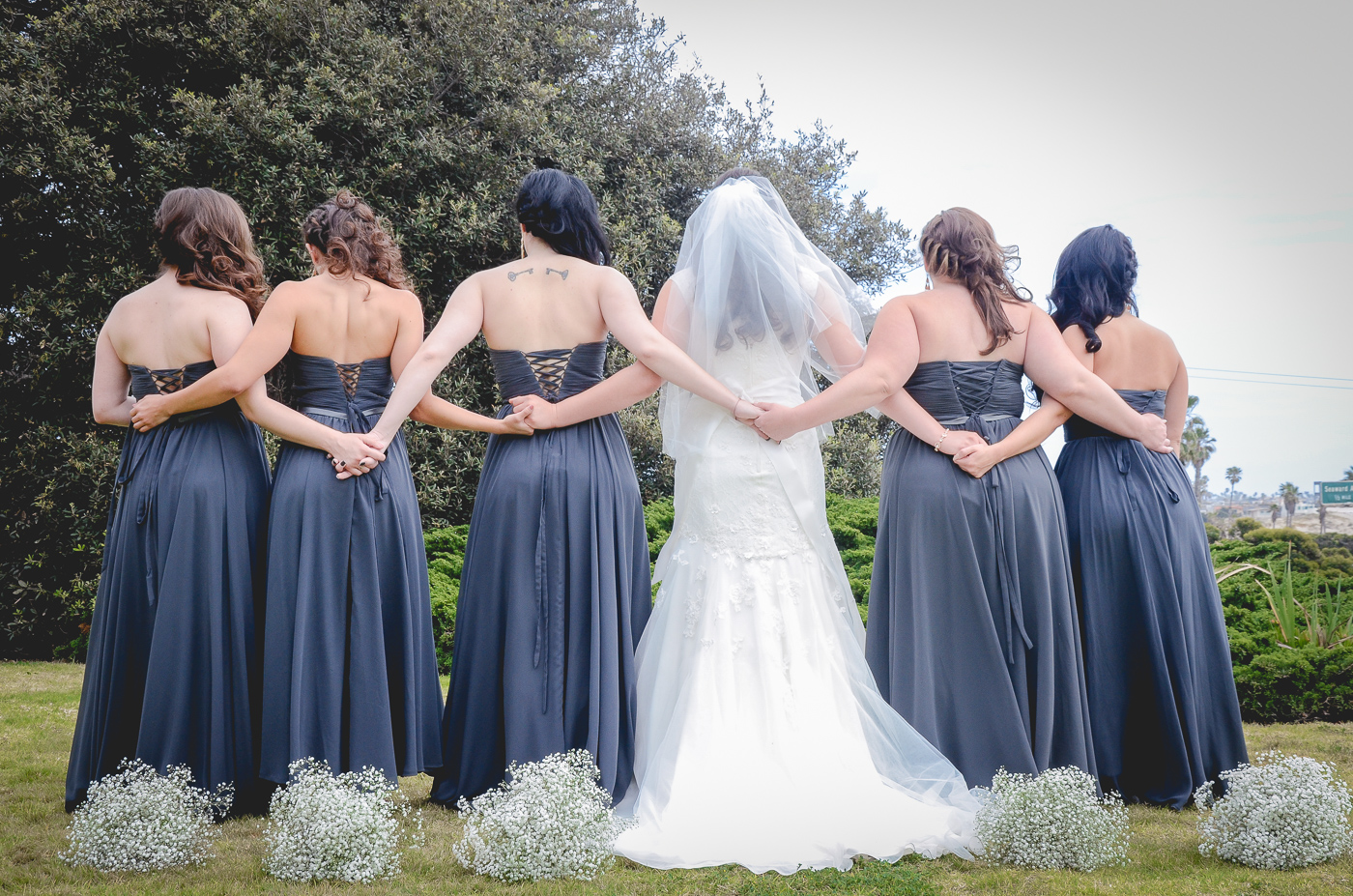 Bride with bridesmaids in grey dresses at wedding ceremony. Finally Forever Photography