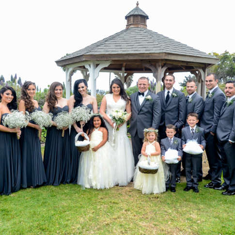 Full wedding party in grey at a beautiful outdoor wedding ceremony. Finally Forever Photography.