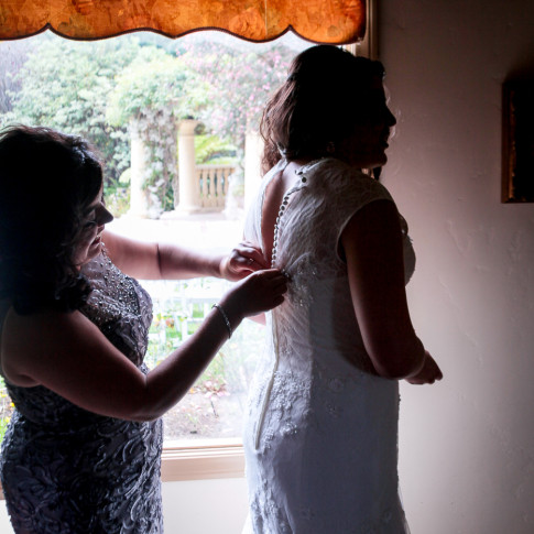 Mother helping bride getting ready before wedding ceremony. Finally Forever Photography