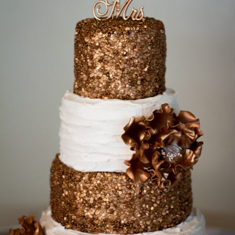 Bronze and cream wedding cake at reception in Pierpont Inn in Ventura, CA.