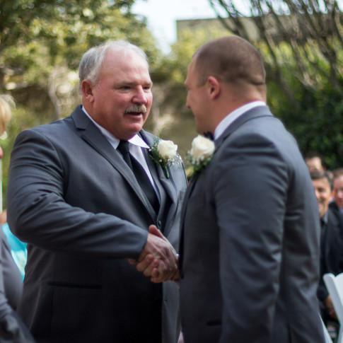 Groom and father shaking hands after walking down the aisle at outdoor wedding ceremony in Ventura, ca.