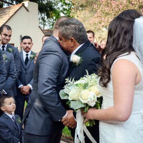 Groom and father of the bride hugging at beautiful outdoor wedding ceremony in Ventura, ca.