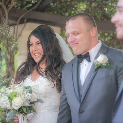 A happy groom smiling at an outdoor wedding ceremony at the pierpont inn in Ventura, CA.