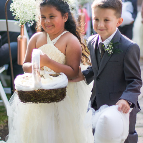 A flower girl and ring barer walk down the aisle after outdoor wedding ceremony at the Pierpont Inn, Ventura, CA.