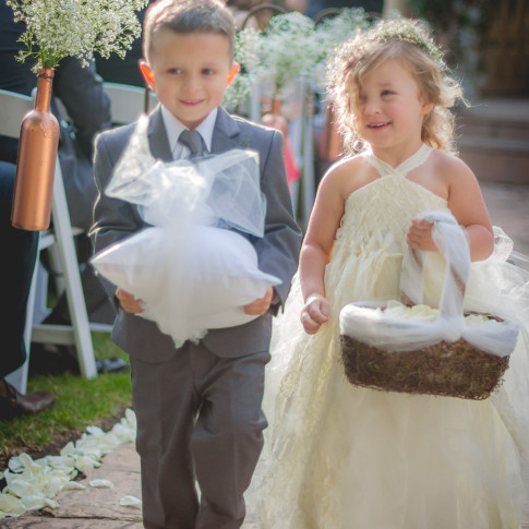 Ring barer and flower girl walk down the aisle at beautiful outdoor wedding in Ventura, ca.