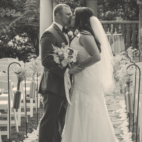 A bride and groom kiss after their beautiful outdoor ceremony at the pierpont inn, Ventura, CA.