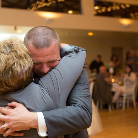 Groom embraces his mother after mother and son dance at wedding reception in Ventura, CA.