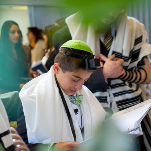 Boy reading torah at bar mitzvah ceremony