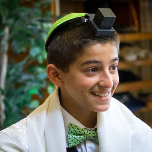 Boy wearing Tefillin during bar mitzvah ceremony